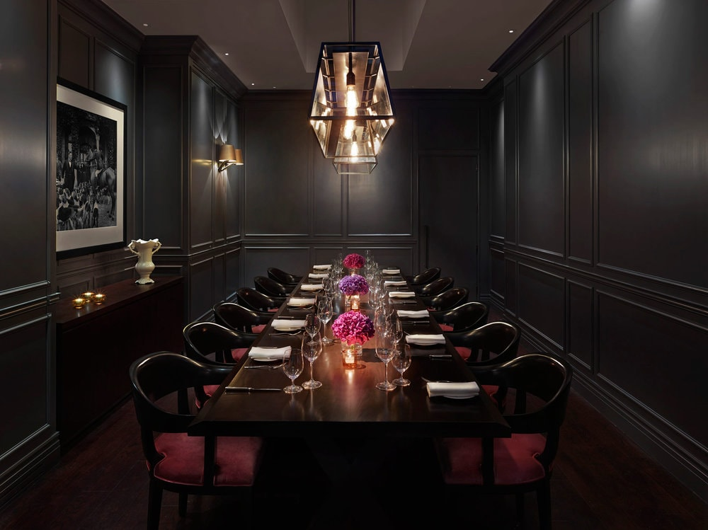 a custom SENTIENT contemporary designed wood dining table and chairs in luxury black private dining room