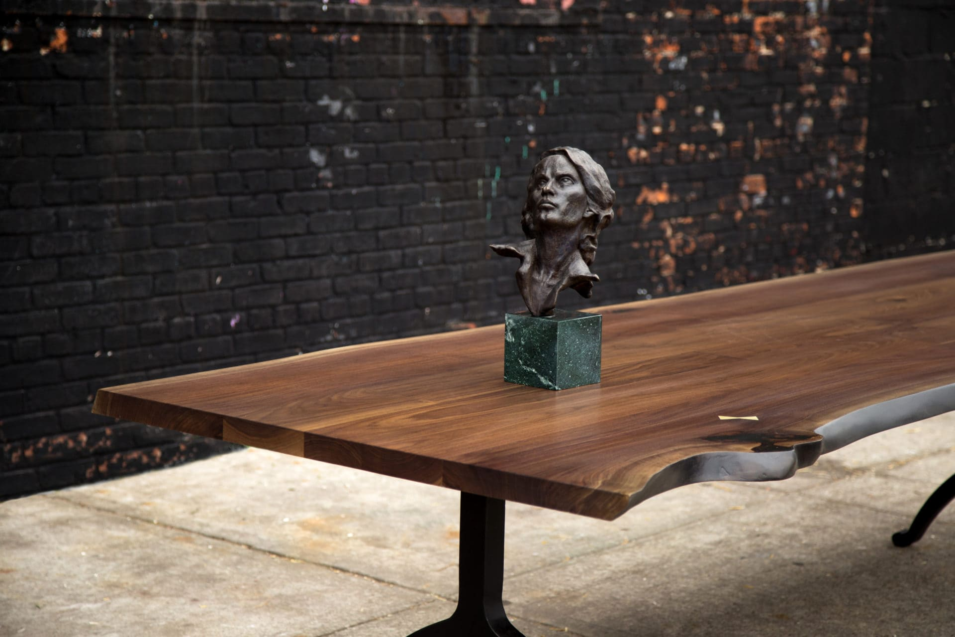 a contemporary designed SENTIENT walnut live edge wood luxury table detail with sculpted bust on top
