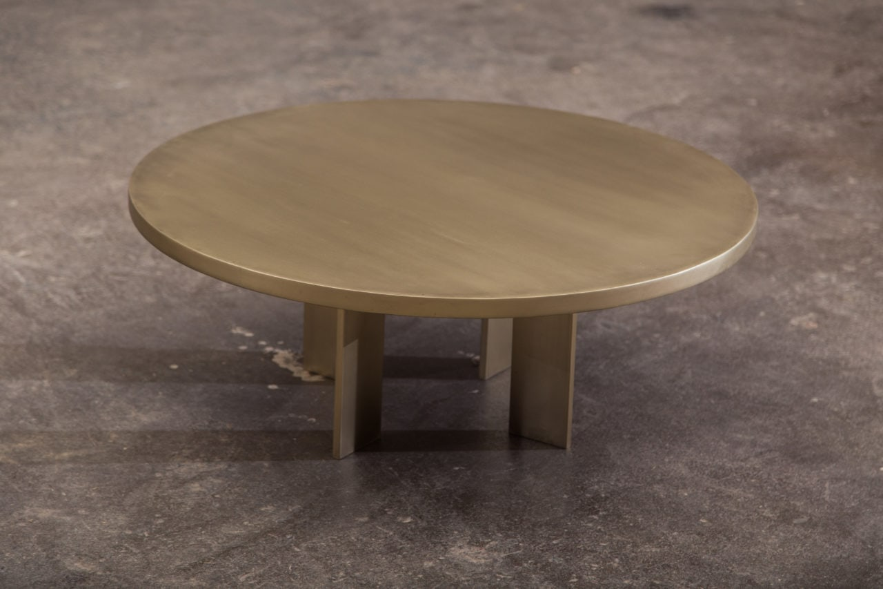 a contemporary designed round four legged luxury antique brass coffee table