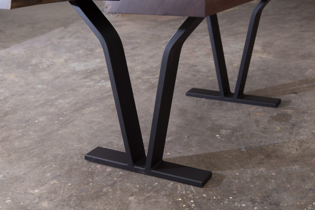 an american black walnut solid live edge luxury table detail with a pair of v-shaped blackened steel legs