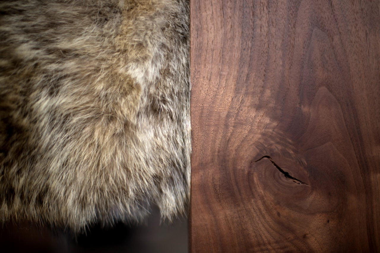 A luxury fur and walnut detail of the SENTIENT contemporary designed caribou custom chair